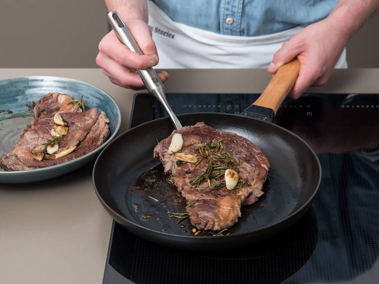 Währenddessen den Backofen auf 60°C vorheizen. Eine gusseiserne Pfanne auf mittlerer bis hoher Stufe erhitzen. Sobald die Pfanne vollständig erhitzt ist, Steaks aus dem Gefrierbeutel nehmen, mit Kräutern und Knoblauch in die Pfanne geben und von beiden Seiten ca. 4 – 5 Min. scharf anbraten. Steaks mit Kräutern und Knoblauch auf einen tiefen Teller geben. Mit einem flachen Teller bedecken und im Ofen bei 60°C ca. 8 – 10 Min. ruhen lassen.