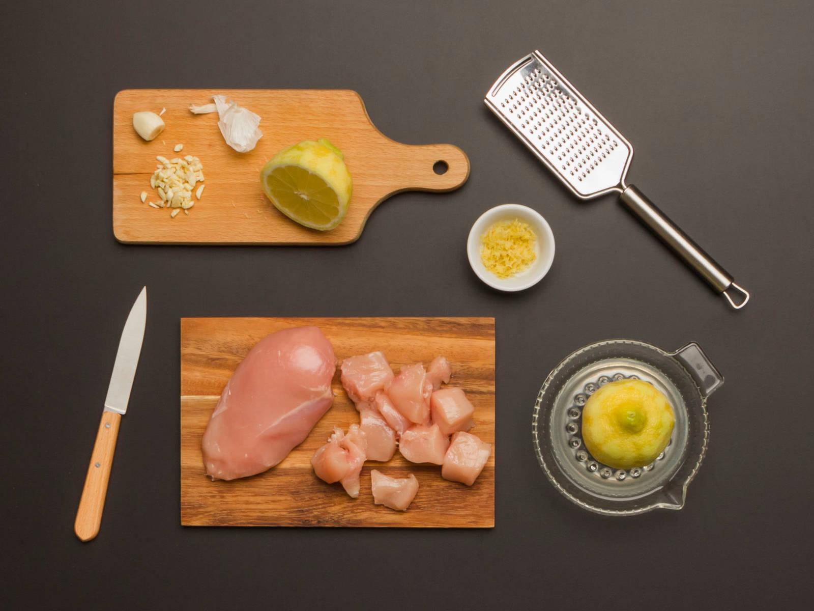 Backofen auf 200°C vorheizen. Knoblauch schälen und fein hacken. Ingwer reiben. Zitrone mit der Reibe abreiben und entsaften. Hähnchenbrüste waschen, abtupfen und in mundgerechte Stücke schneiden.