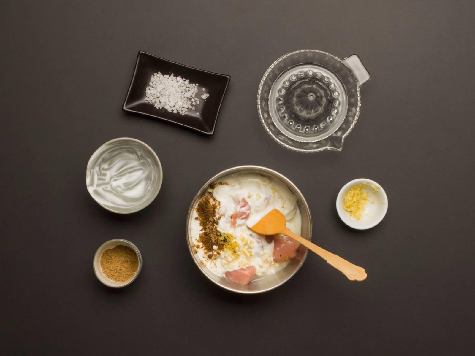 In einer großen Schüssel Hähnchen, Joghurt, Ingwer, Hälfte des Knoblauchs, Hälfte des Garam Masalas, Zitronensaft und -abrieb sowie etwas Salz vermengen.