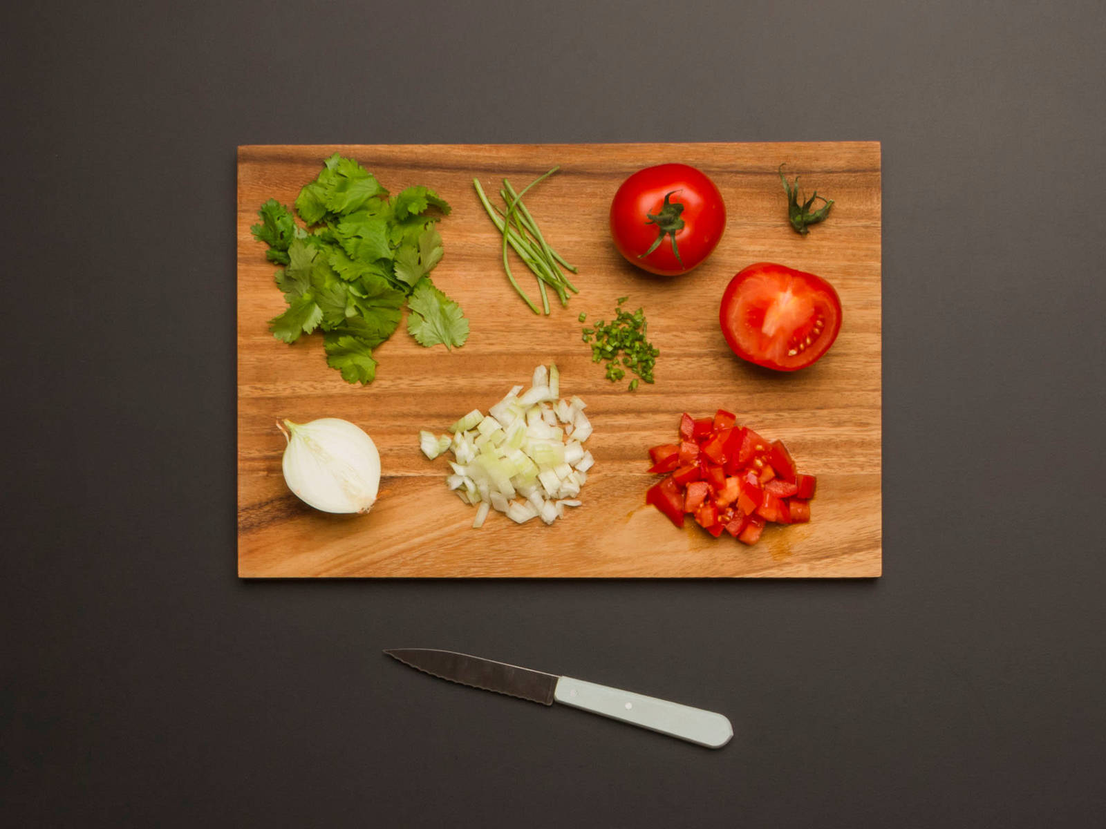 Tomaten in kleine Würfel schneiden. Zwiebel schälen und fein würfeln. Korianderblätter vom Stiel zupfen und Stiele fein hacken.