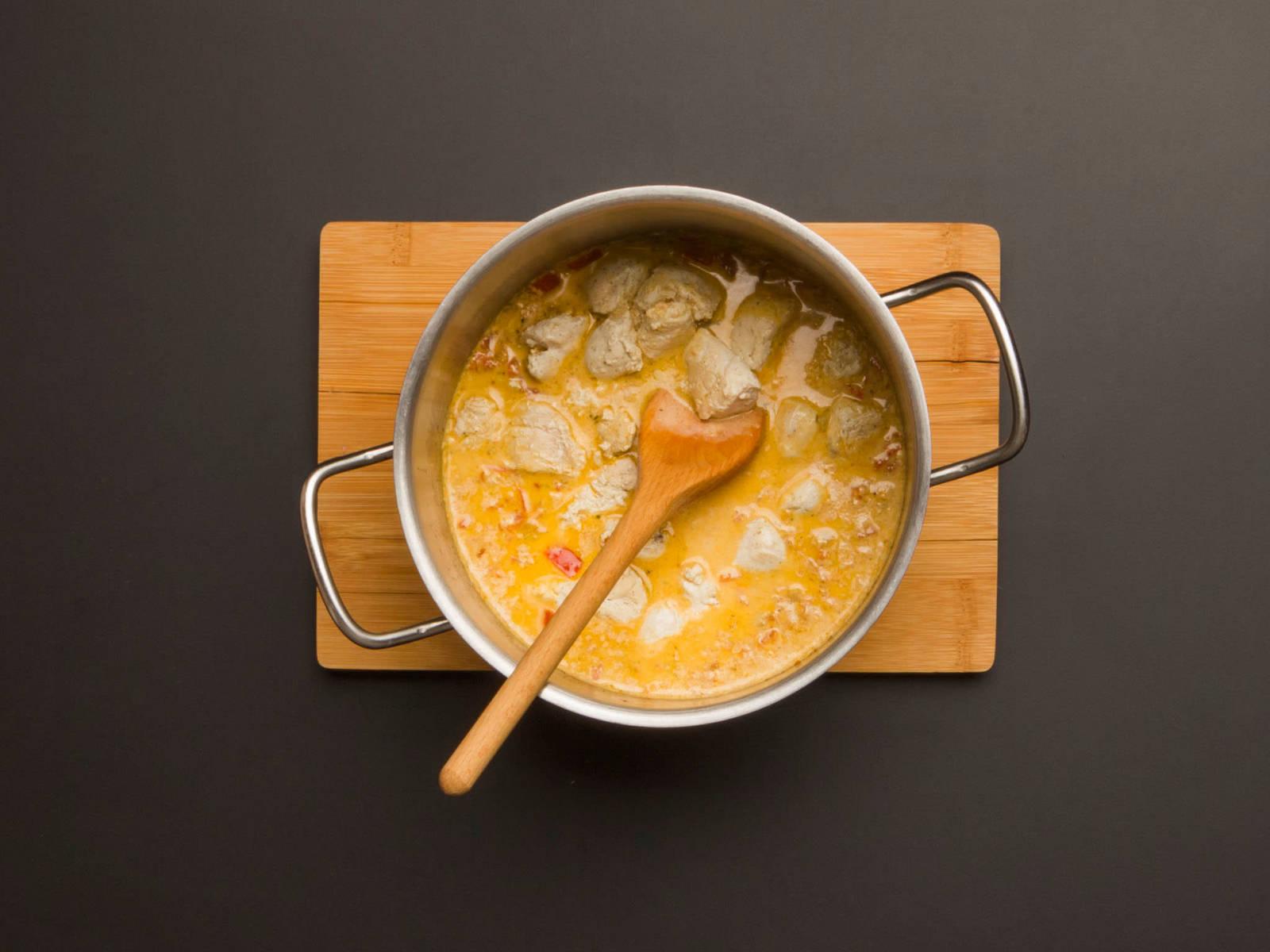 Gebackenes Hähnchen in die Pfanne geben und gut vermengen. Reis auf einer Servierplatte anrichten, Zitronen-Hühnchen Tikka Masala obenauf geben und mit Korianderblättern garnieren.