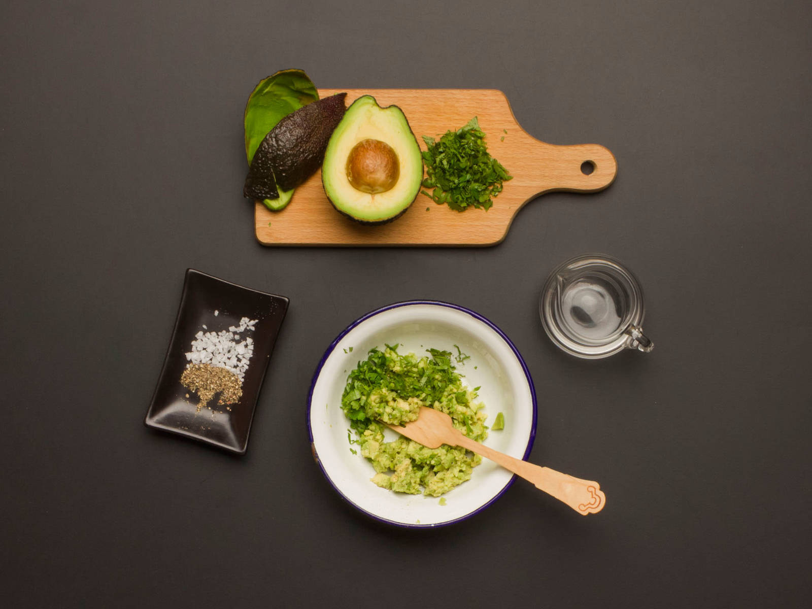 Cut avocado in half and remove pit. Scoop out flesh, place in a bowl, and mash with a fork. Add half of cilantro and the white wine vinegar to bowl, and mix well to combine. Season to taste with salt and pepper.