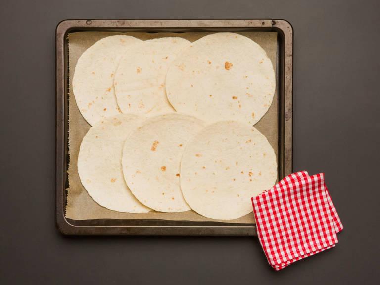 将小麦面饼放在平整的工作台上。铺上捣碎的鳄梨,香菜饭,番茄丁,小平菇和车达奶酪。