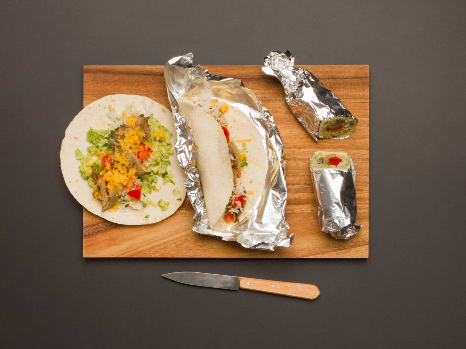 Fold the tortillas in from the sides and then roll forward with your thumbs until burrito is tightly rolled. Wrap with aluminum foil and cut in half. Serve garnished with reserved cilantro leaves.