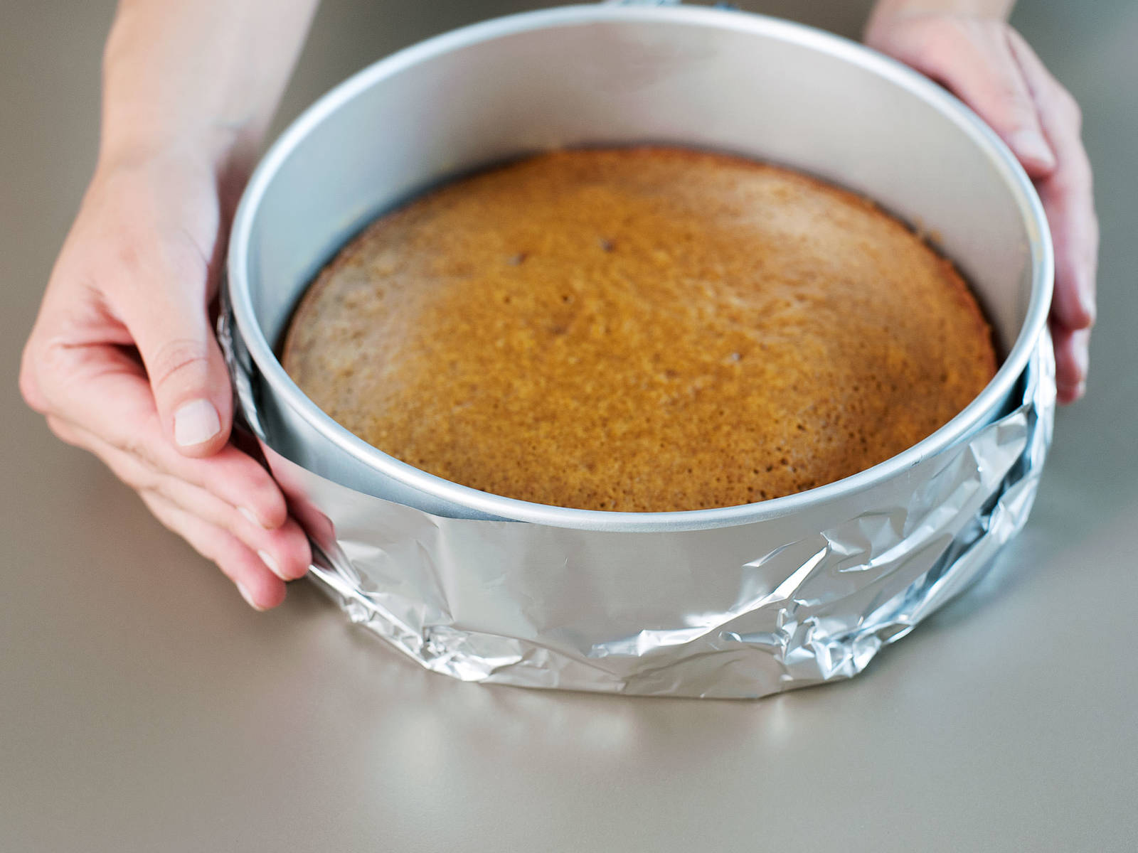 Den Boden der Backform mit 2 Bahnen Alufolie kreuzweise von außen umwickeln. Etwas Wasser zum Kochen bringen. Die Ofentemperatur auf 160°C reduzieren.