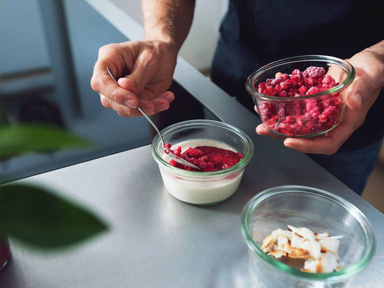 Return raspberry sauce to pan and reheat over medium heat. Add remainder of frozen berries to blender and pulse for approx. 10 – 15 sec. Garnish cream with raspberry sauce, frozen raspberry pieces, and toasted coconut flakes, if desired. Enjoy!