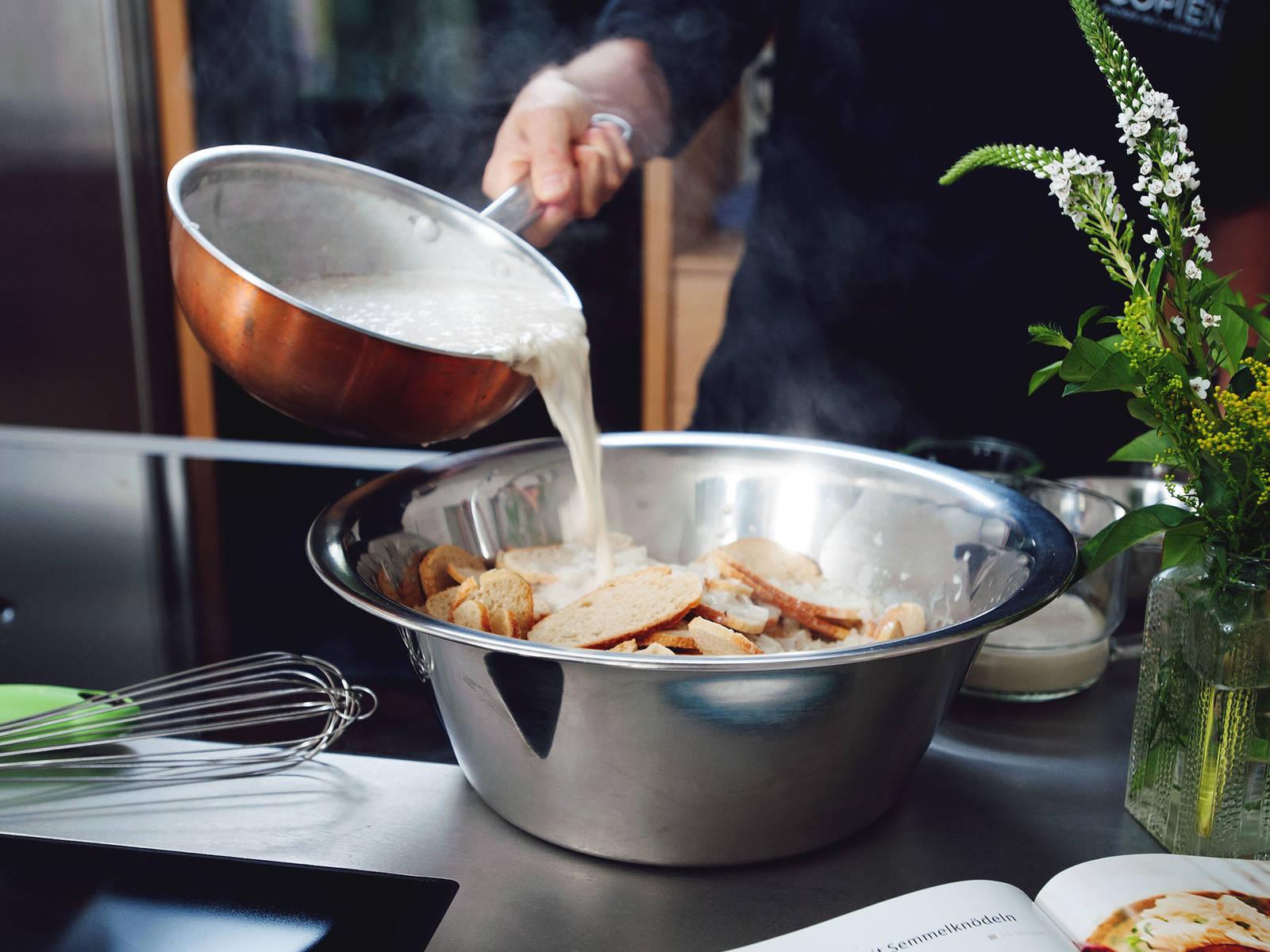 Knödelbrot in eine große Schüssel geben und die erhitzte Mandel-Dinkel-Milch darübergießen.