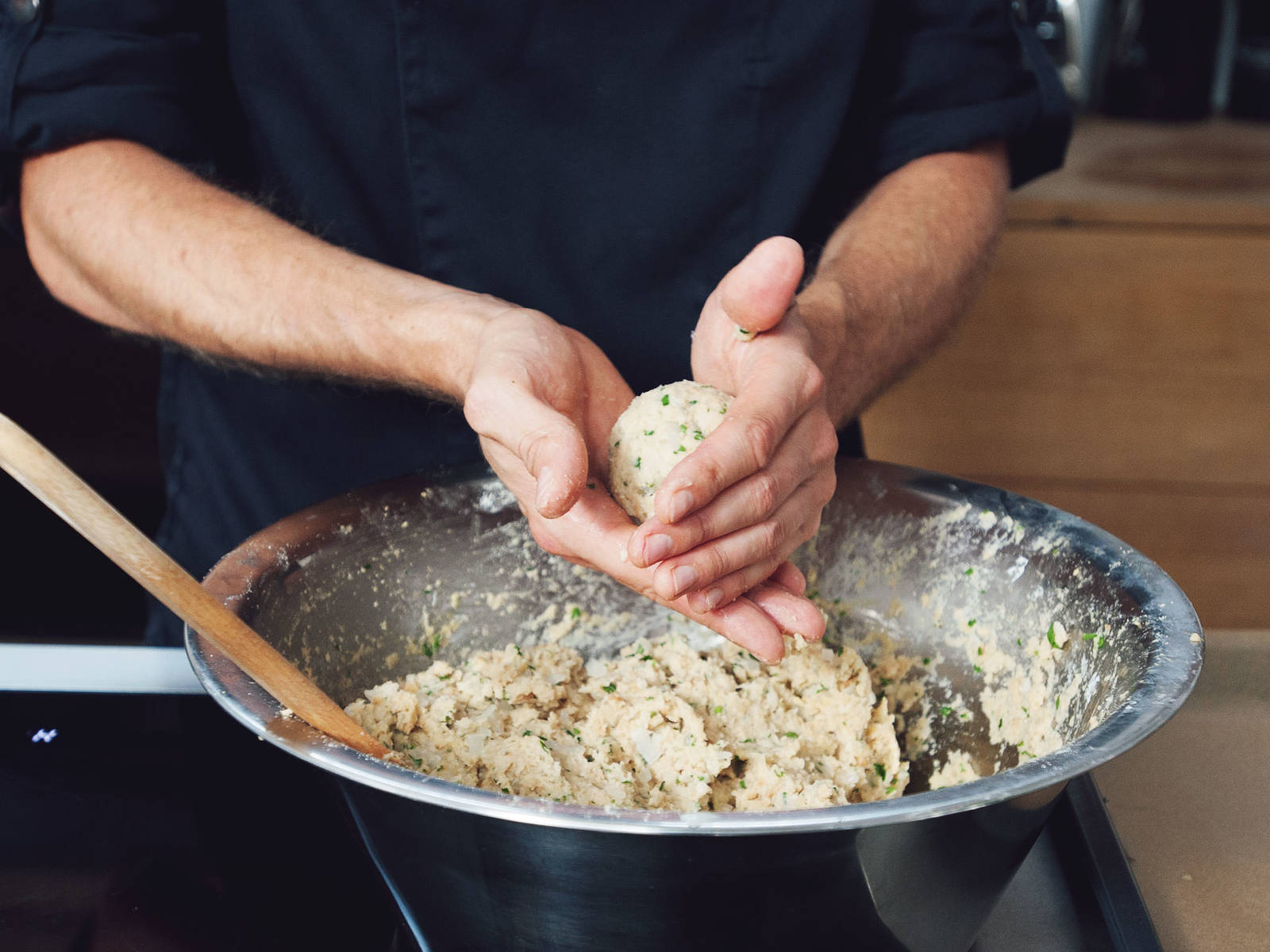 In a large saucepan, bring water to boil and add salt. Turn down heat until the water is hot but does not bubble anymore. Slightly wet hands and form a ball the size of a golf ball out of dumpling dough. Transfer first test dumpling to the saucepan. If it falls apart, add more flour and breadcrumbs to the dough.