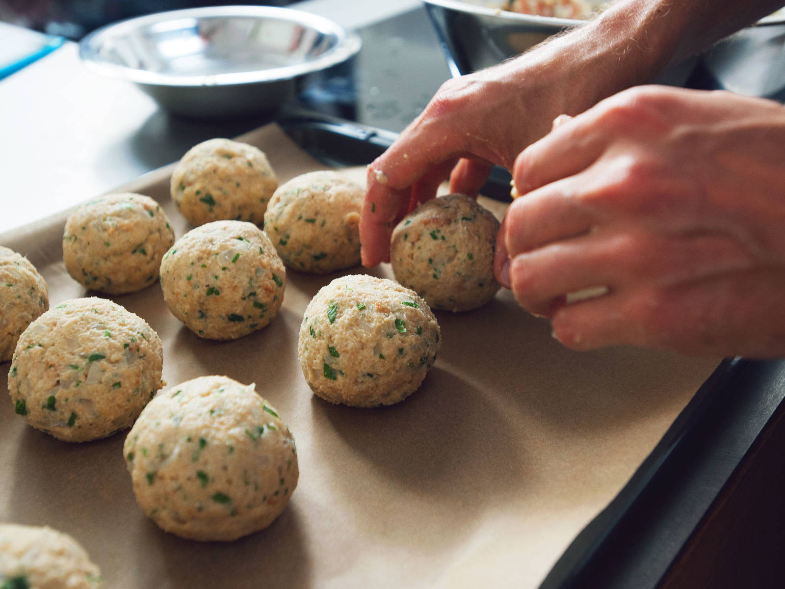 When test dumpling succeeds, form balls out of remaining dough and place them on a baking sheet lined with parchment paper. Add all bread dumplings to saucepan, being careful to arrange them so that they don't lie on top of each other. Let them simmer for approx. 20 min. Pay attention that water doesn't boil again.