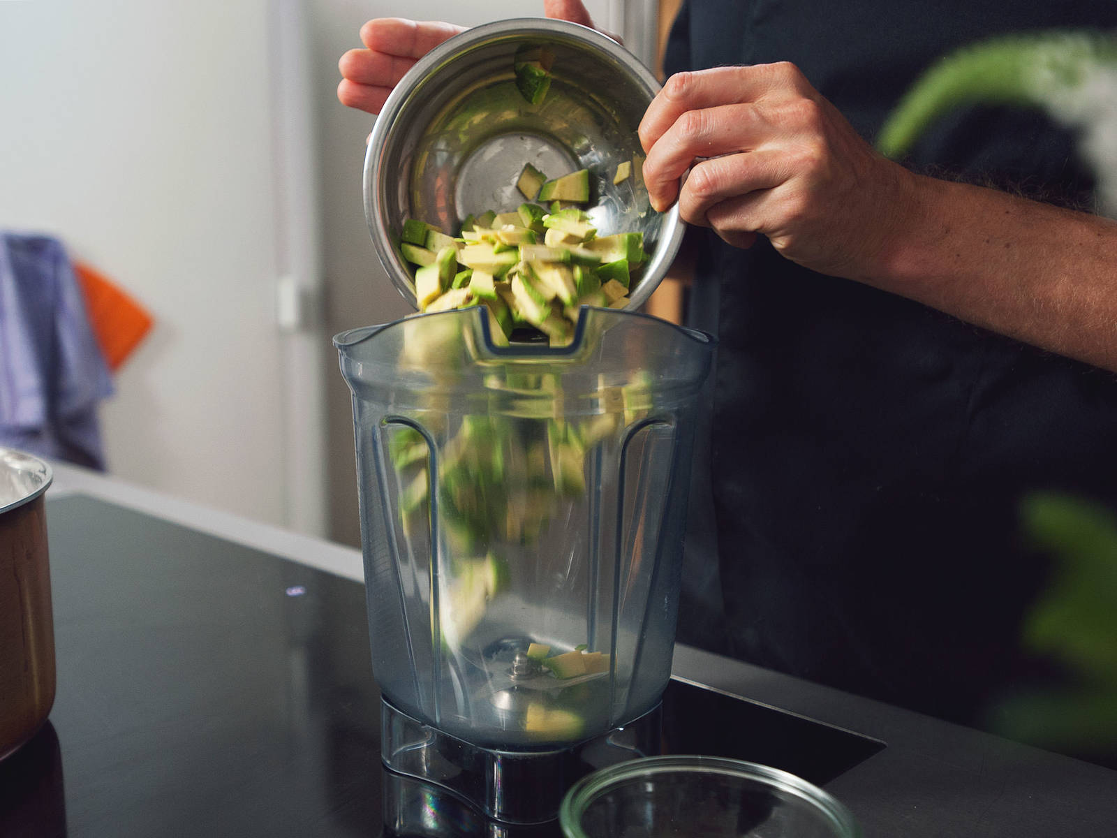 In the meantime, make the sauce and prepare the toppings. Peel avocado and remove the pit. Cut avocado flesh into small pieces. Cut tomatoes into quarters and roughly chop arugula. Set tomatoes and arugula aside for serving. Peel garlic clove and chop onion. Transfer avocado to a food processor or blender.