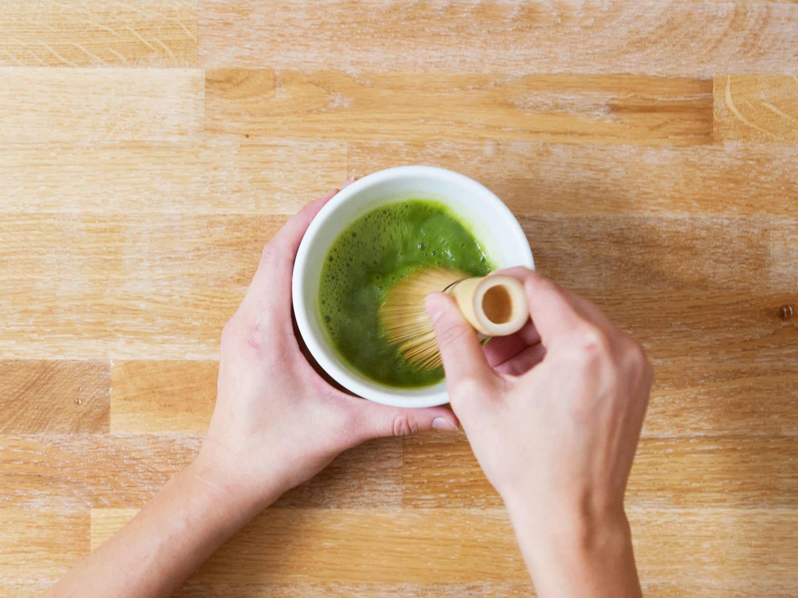 水煮沸后放凉5分钟。在一个小碗中,放入抹茶和2汤匙热水。用抹茶搅拌器小心搅拌,直至呈糊状。倒入剩余的水,轻轻搅拌30-60秒。