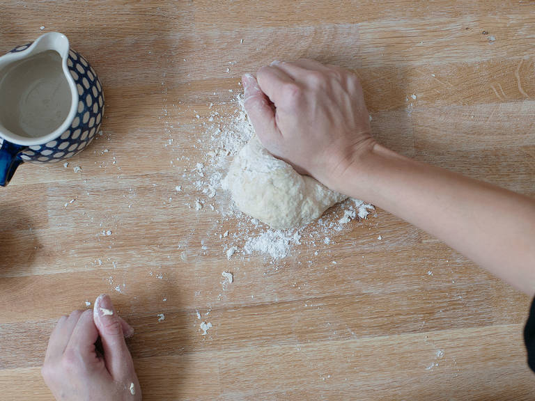 Ofen auf maximale Temperatur vorheizen (230°C - 300°C) und Pizzastein, falls vorhanden, in den Ofen legen. Alternativ, Backblech für das Vorheizen im Ofen lassen. Mehl und etwas Salz sieben und in einer großen Rührschüssel mit Olivenöl und lauwarmen Wasser ca. 5 Min. zu einem geschmeidigen Teig kneten.