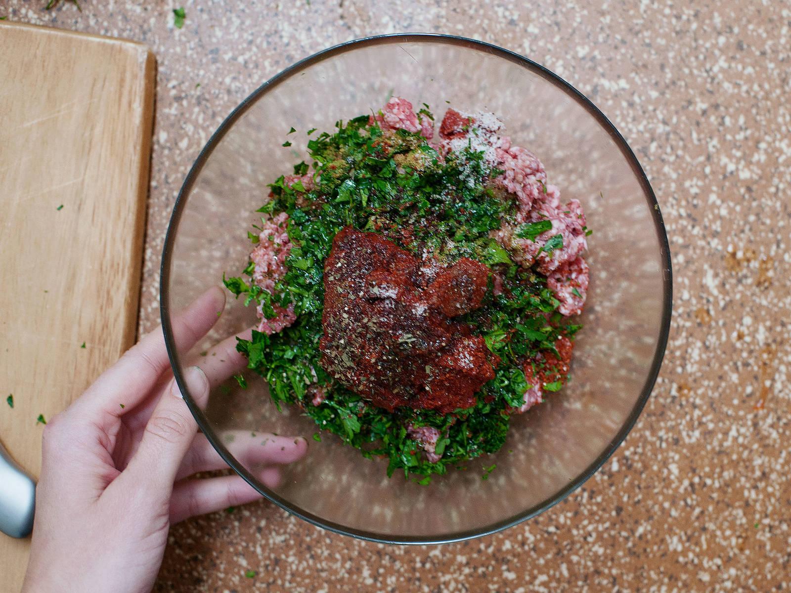 将平叶欧芹切碎。将半份置于一旁,稍后用于装饰。在一个大碗中,混合羊肉末、番茄丁、半份欧芹末、番茄酱、野生蒜粉、蒜油、橄榄油、辣椒粉、辣椒末和莳萝。用盐与胡椒调味。