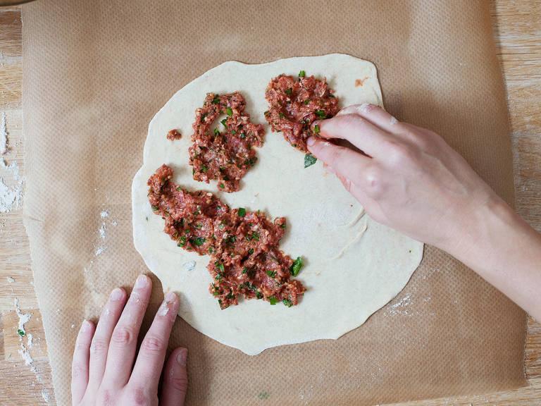 将羊肉混合我薄薄地抹到面皮上,用指尖轻轻压下。将披萨连烘焙纸一起放入烤箱中,小心地将其放到热好的烤盘中。烤5-8分钟,或直至披萨稍微起泡,且边缘变棕。重复操作,直至用完剩余的面团和馅料。