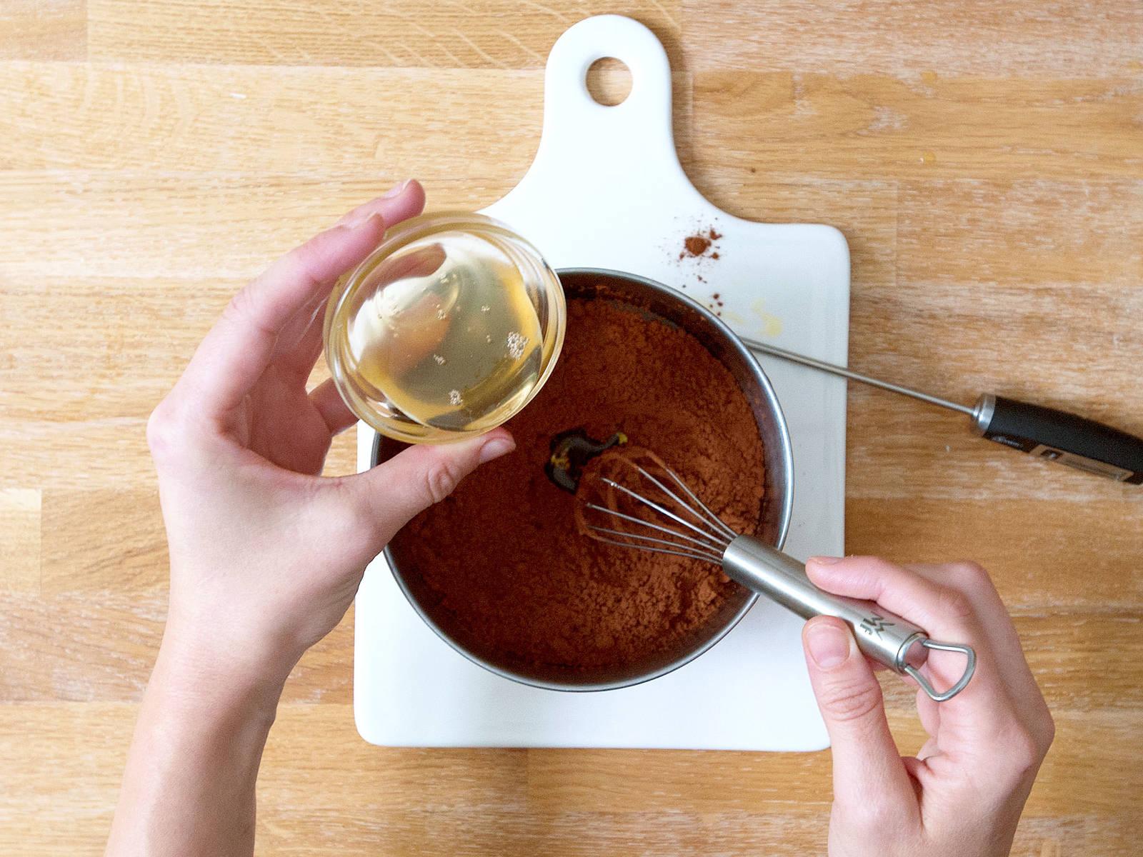 Kakaobutter in einer hitzebeständigen Schüssel über einem Topf mit köchelndem Wasser schmelzen bis die Mischung eine Temperatur zwischen 46 - 49°C erreicht. Geschmolzene Kakaobutter vom Herd nehmen und auf 27°C abkühlen lassen. Kakaopulver und restlichen Reissirup einrühren und die Mischung erneut auf 32°C erhitzen.
