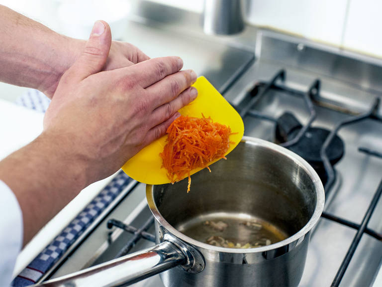 Einen weiteren Topf bei mittlerer Hitze erwärmen und etwas Butter darin zerlassen. Nun vorbereitete Schalotten, Ingwer, Knoblauch und Karotten andünsten, bis sie leichte Röstaromen entwickeln.