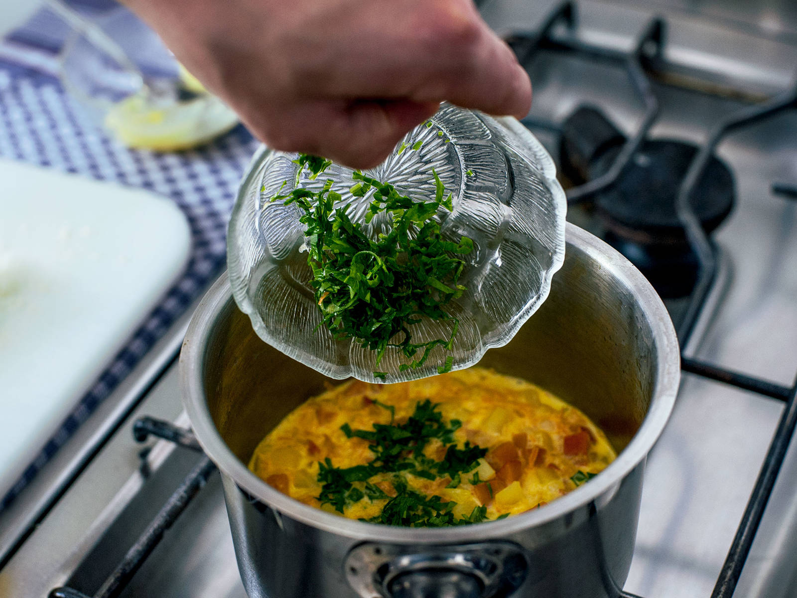 在锅中加入一些奶油和焯过土豆南瓜的汤水,煮沸。倒入南瓜块、土豆块和帕玛森奶酪,煮5-7分钟。加入欧芹、芝士、肉豆蔻、盐与胡椒调味。拌入南瓜籽。