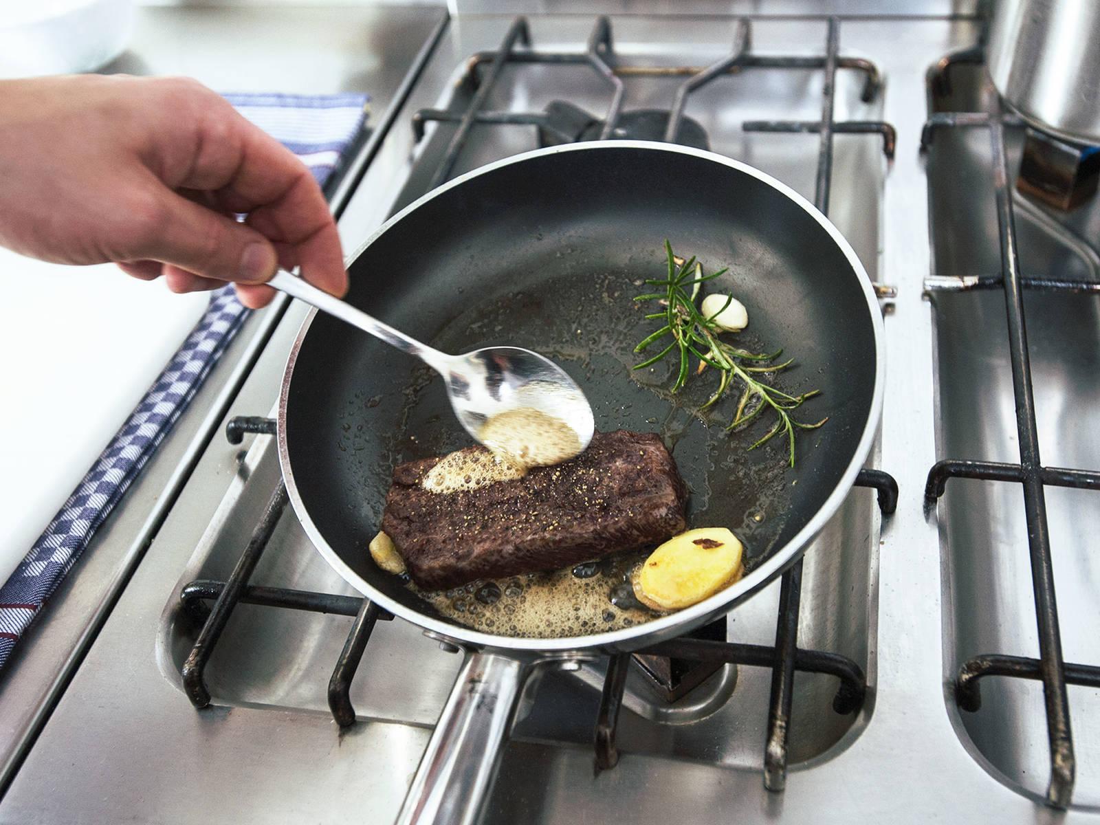 中火加热煎锅,放入些许黄油、蒜、姜和迷迭香。倒入鹿肉,翻炒加热,使其完全裹上黄油,然后撒胡椒调味。