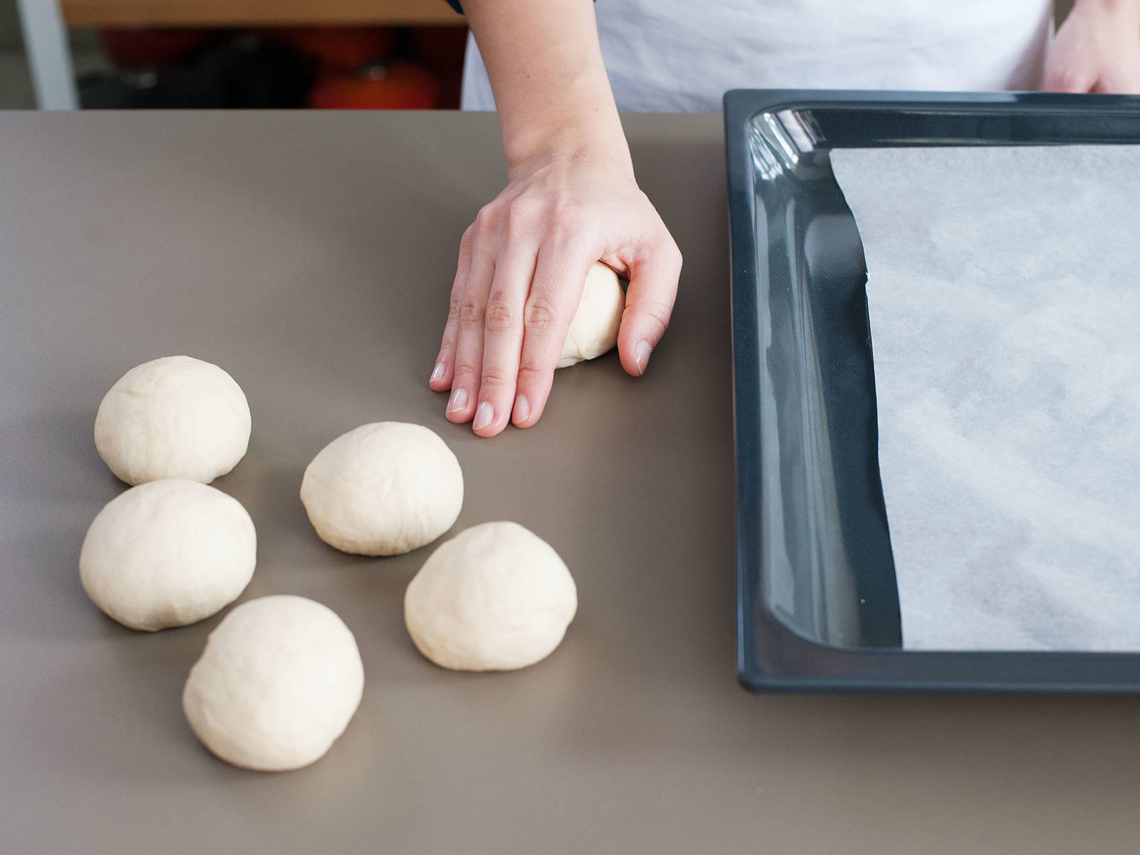 Then, roll dough pieces into smooth balls, transfer back to parchment-lined baking sheet, and cover with a damp kitchen towel. Let rise for another approx. 30 min. in a warm place.