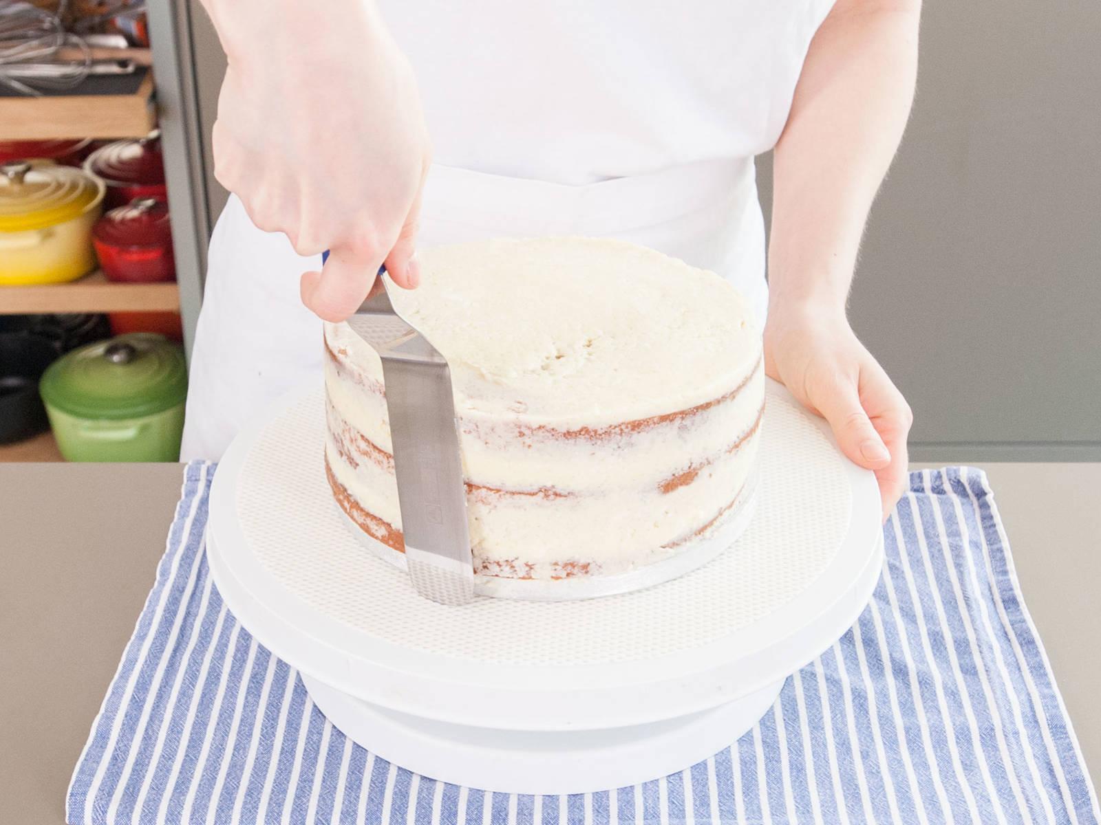 在每层蛋糕的顶部和周边都涂上薄薄一层霜饰。清洁橡胶刮刀,避免给奶油糖霜弄上更多碎屑。将每层蛋糕放到冰箱中,至少冷藏30分钟,好让霜饰凝固。