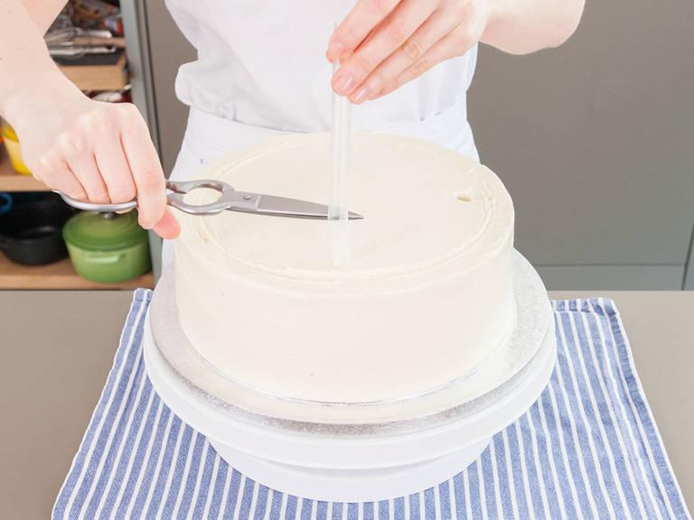 Auf der Markierung des untersten Tortenstockwerkes, werden mit gleichmäßigem Abstand die Strohhalme oder Tortendübel durch alle Schichten in die Torte gesteckt. Markiere den Halm oder Dübel auf Höhe der Tortenoberfläche. Entferne sie aus der Torte und schneide die Halme oder Dübel an der markierten Stelle ab. Wiederhole den Vorgang mit dem mittleren Stockwerk und benutze 3 Strohhalme oder Tortendübel. Die Löcher können mit Buttercreme versiegelt werden.