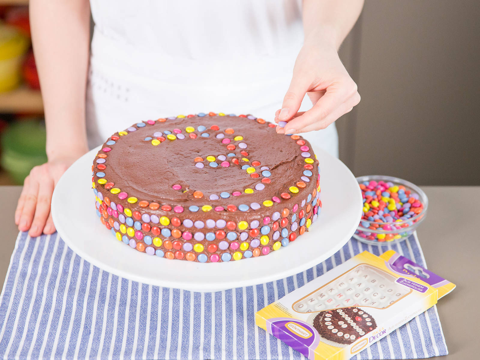 Frost cooled cake with buttercream and over in Smarties by gently pressing the candies into buttercream.