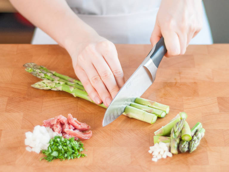Roughly chop asparagus and separate stalks. Finely chop onions, garlic, and parsley; cut Prosciutto into strips.