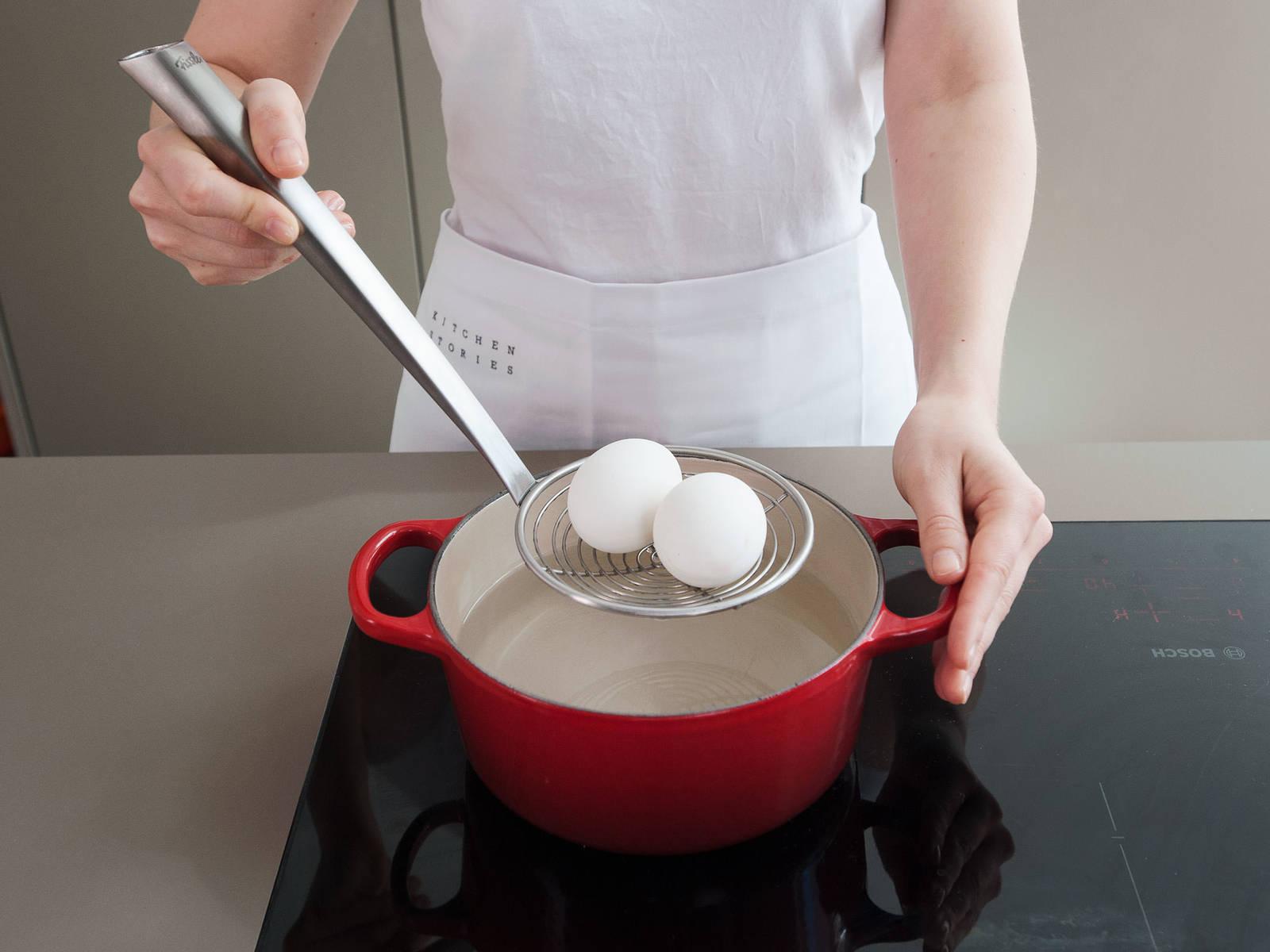 在小平底锅中倒入盐水,放入两个鸡蛋,煮上8-10分钟,将鸡蛋煮至全熟。