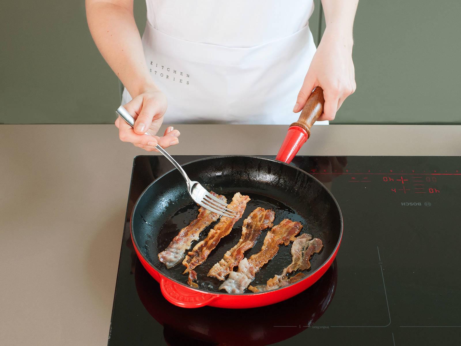 在一只大煎锅里,用中高火将培根的两面各煎一至两分钟,直至培根表面卷起。移至垫有纸巾的盘子上吸干多余的油脂。