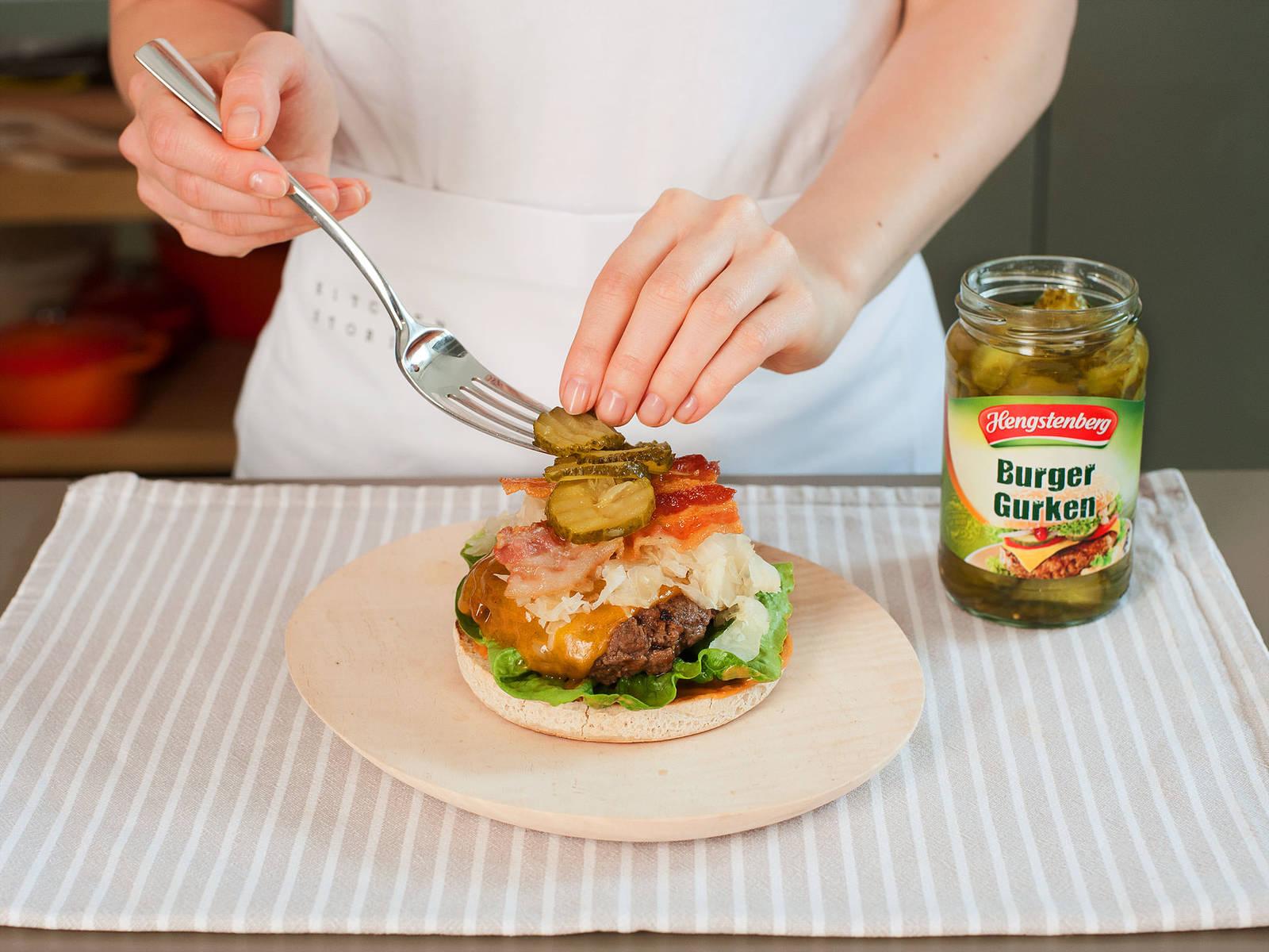 与此同时,清洗沥干生菜。用中火将一只干净的大煎锅加热,然后加入微量的植物油,将汉堡面包每面烤60至90秒。将番茄酱和芥末混在一起,涂一层在下层的面包上。依次铺上生菜、肉饼、酸菜、培根和酸黄瓜。最后涂上酱汁,盖上面包享用!