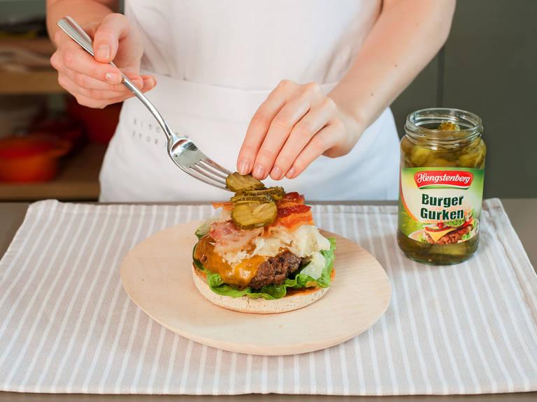 In der Zwischenzeit Salat waschen und trocknen. Burger-Brötchen in einer großen sauberen Pfanne bei mittlerer Hitze in etwas Pflanzenöl ca. 60 – 90 Sek. pro Seite rösten. Ketchup und Senf vermengen und auf der unteren Hälfte des Brötchens verteilen. Anschließend Burger-Patty, Salat, Sauerkraut, Speck und Gewürzgurken nacheinander auf die untere Brötchenhälfte legen und mit der oberen Brötchenhälfte abschließen. Guten Appetit!