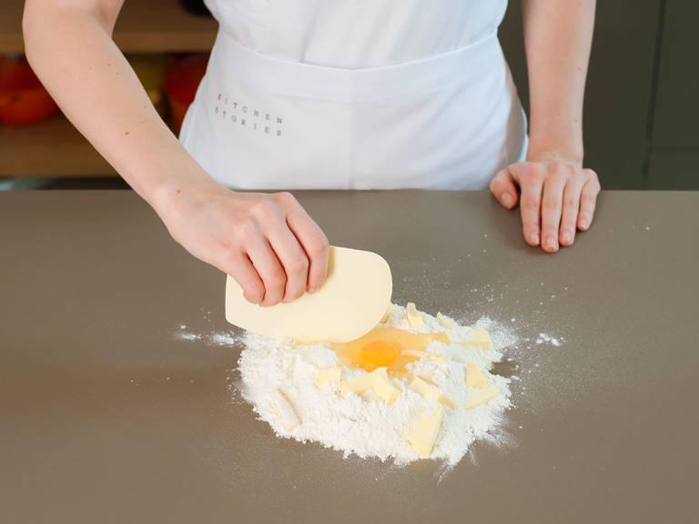 混合面粉和盐。倒到工作台上,堆成土丘状,在中间挖出一个坑。将鸡蛋打入其中。黄油切块,分放在面粉上,然后用切面刀将黄油和面粉混合。接着,用手充分搅和所有材料,直至面团光滑均匀。将面团压成扁平圆盘状。用塑料膜将其裹住,放入冰箱中,冰镇30分钟。