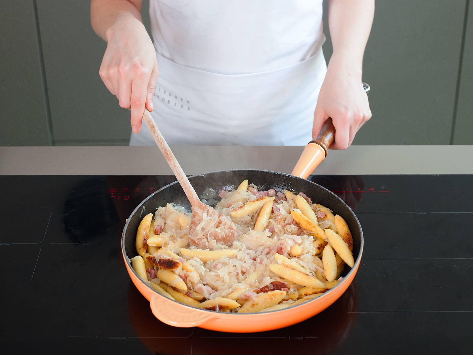 在大煎锅中,中火融化剩余的黄油。倒入土豆饺子,翻炒3-5分钟,直至饺子两侧皆呈金棕色。倒入酸菜,与饺子混合均匀,然后持续翻炒3-5分钟,直至食材受热均匀。可视个人喜好,饰以新鲜欧芹碎装盘。尽情享用吧!