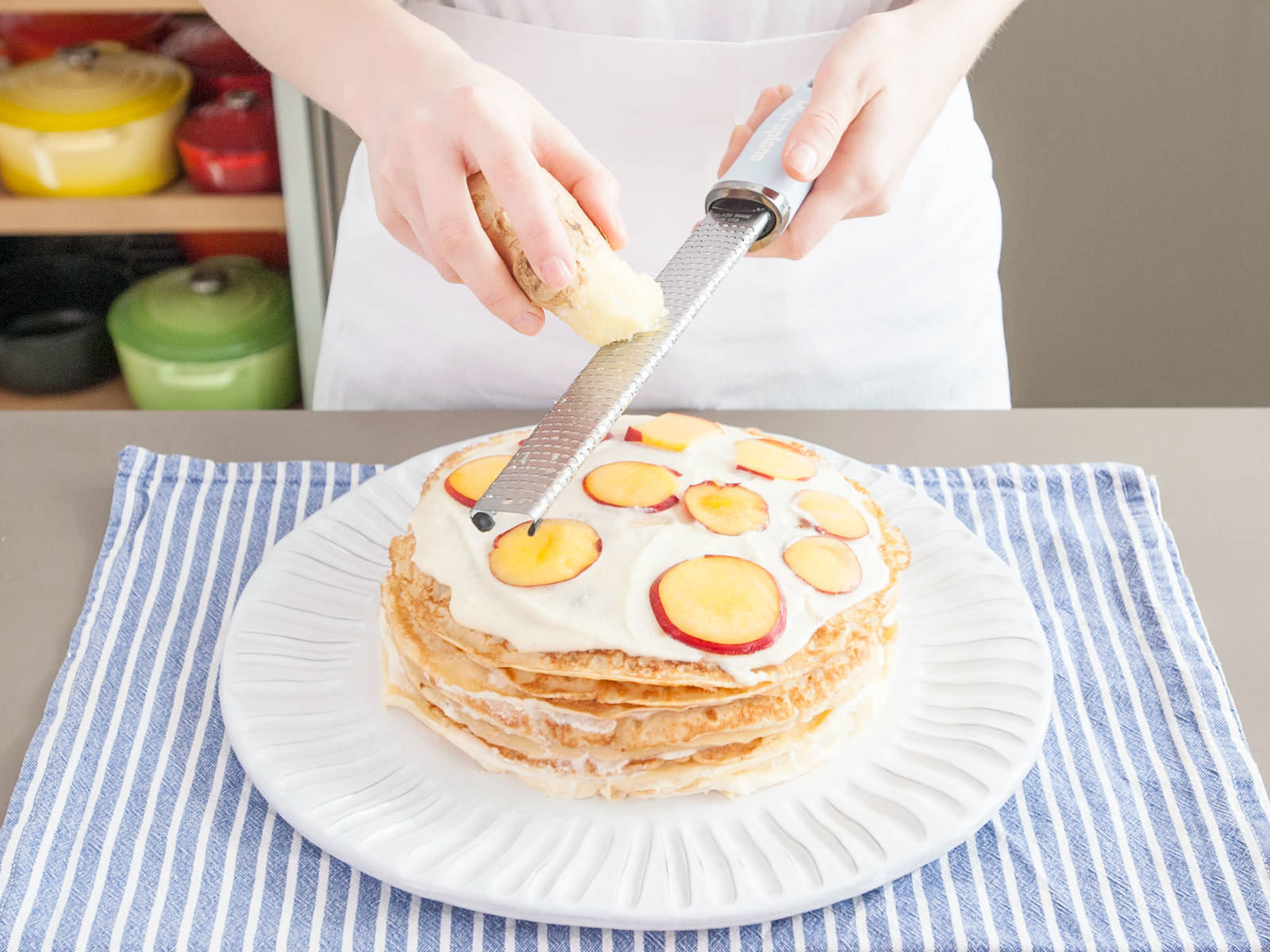 To assemble cake, slice nectarines thinly with a mandolin. Place one crêpe on a serving plate, then spread about 1/4 cup of pastry cream filling on top, and top with another crêpe. Continue this way until all crêpes are used, saving your best looking one for last. Every fourth crêpe or so, top pastry cream with a layer of nectarine slices and grated ginger to taste.