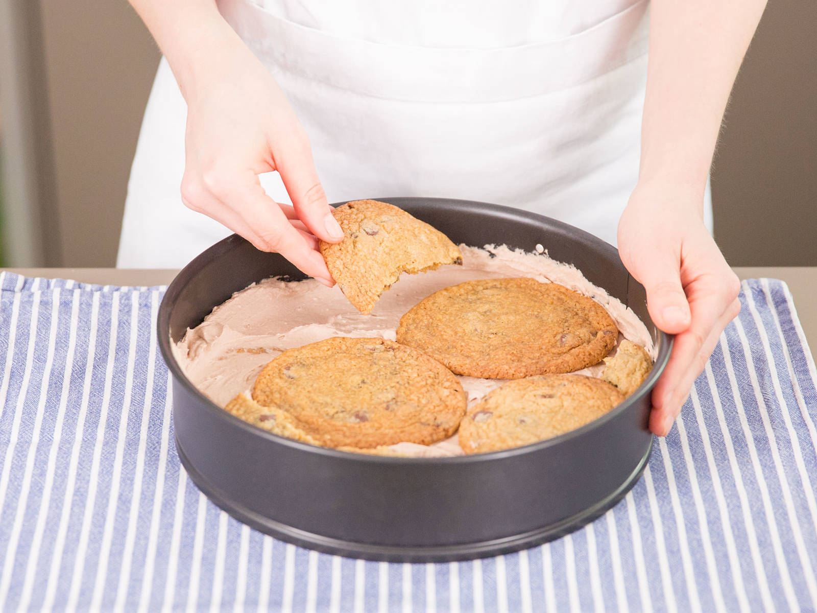 Eine dünne Schicht Schlagsahne auf dem Boden der Springform verteilen, mit einer Schicht Cookies bedecken. Dabei so wenig freie Stellen wie möglich lassen. Cookies in Stücke brechen, um Lücken zu füllen. Eine gleichmäßige Schicht Schlagsahne auf den Cookies verteilen, mit einer weiteren Schicht Cookies bedecken. Weiter schichten bis knapp zum oberen Rand der Form. Mit einer Schicht Sahne abschließen. Kuchen mit Klarsichtfolie bedecken und über Nacht in den Kühlschrank stellen. Zum Servieren mit einem scharfen Messer am Rand entlang fahren und Kuchen aus der Form heben. Vor dem Servieren mit einem Sparschäler etwas Schokolade obenauf raspeln.