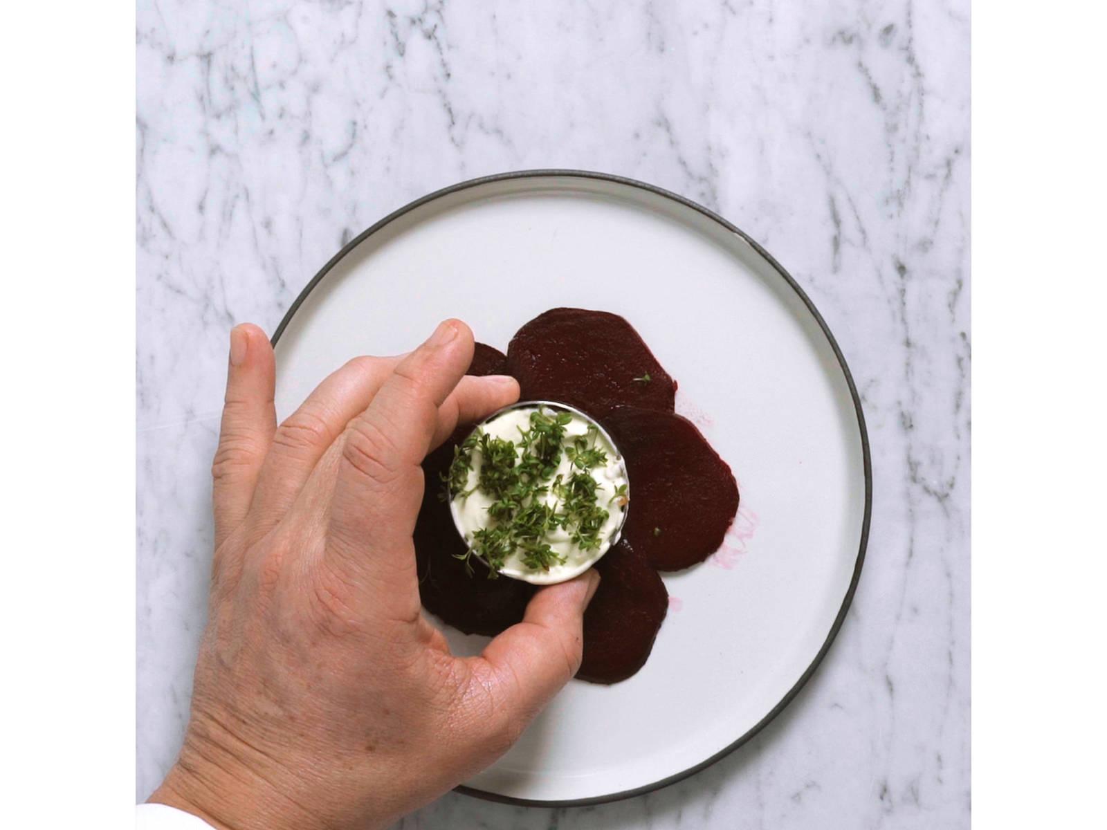 Rote-Bete-Scheiben kreisrund auf Serviertellern auslegen. Lachs-Tartar mithilfe eines Servierrings mittig darauf platzieren und vorsichtig festdrücken. Einen Klecks Wasabi-Creme obenauf geben. Servierring vorsichtig entfernen.
