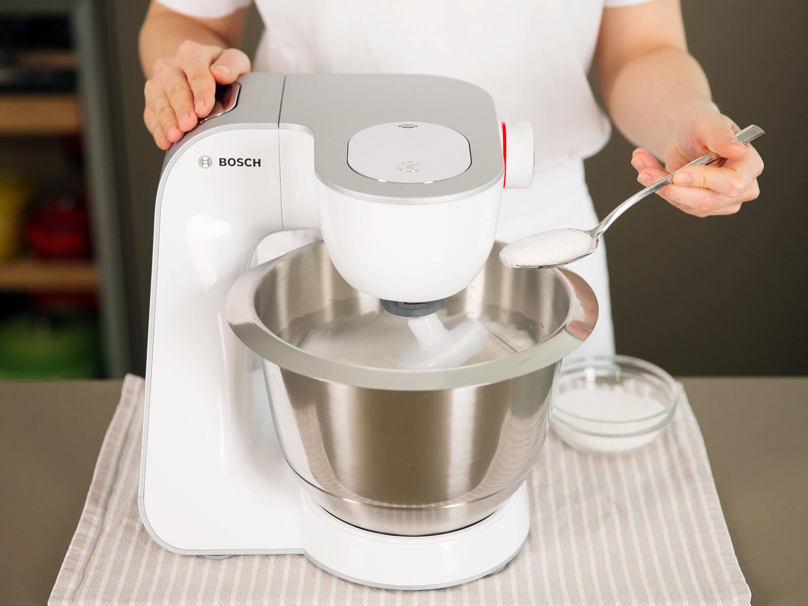 Während der Kuchen im Backofen ist, Eiweiß in einer sauberen Schüssel bei mittlerer Geschwindigkeit aufschlagen. Sobald es anfängt zu schäumen, Salz und Zitronensaft hinzugeben. Nach und nach Geschwindigkeit erhöhen, bis sich weiche Spitzen bilden. Anschließend Zucker langsam hinzugeben, bis das Baiser fest und glänzend ist.