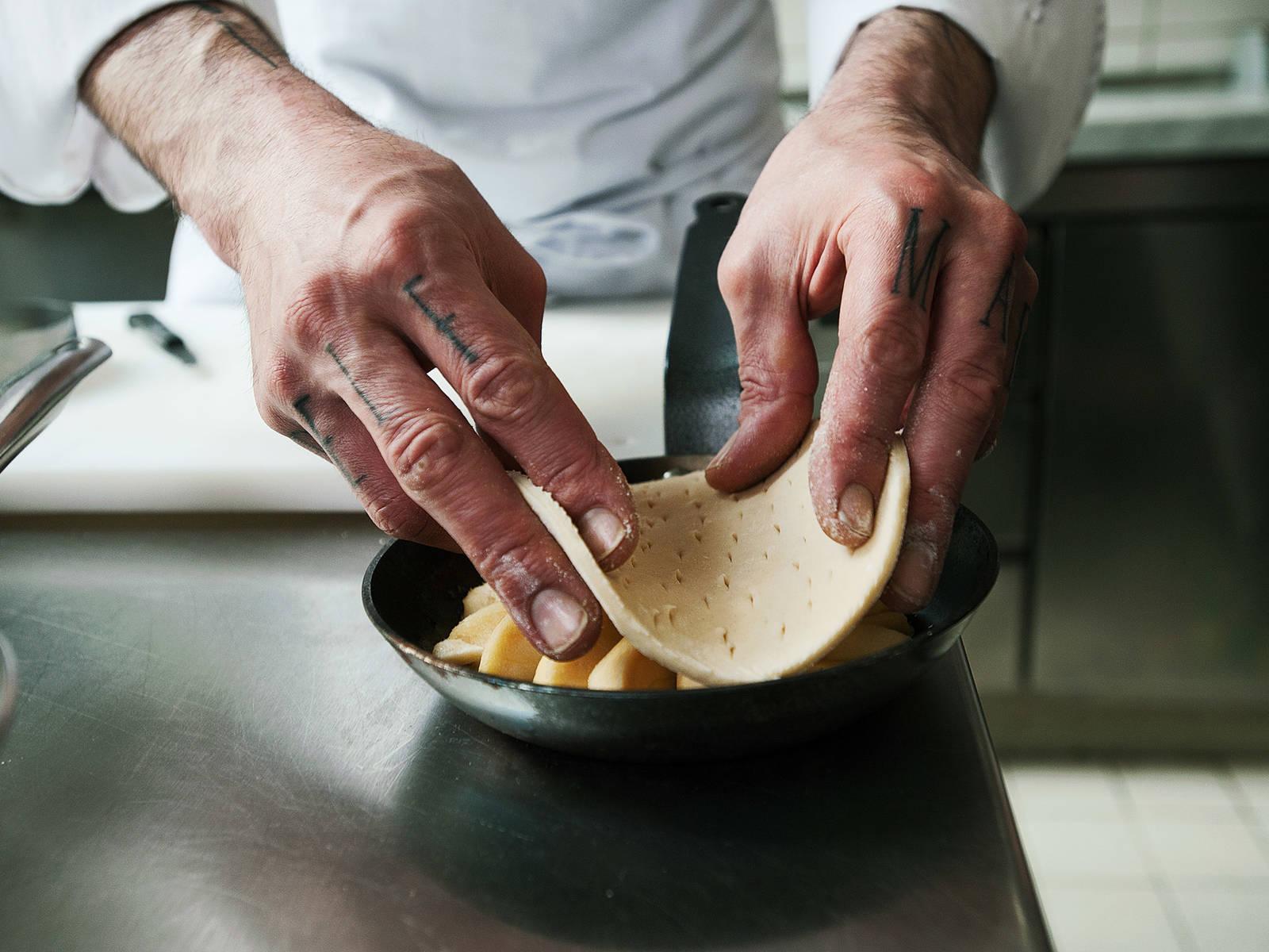 将酥皮切成可覆盖住苹果片的大小,用刀尖戳出纹路。将酥皮放到苹果上,轻轻按压至完全覆盖。