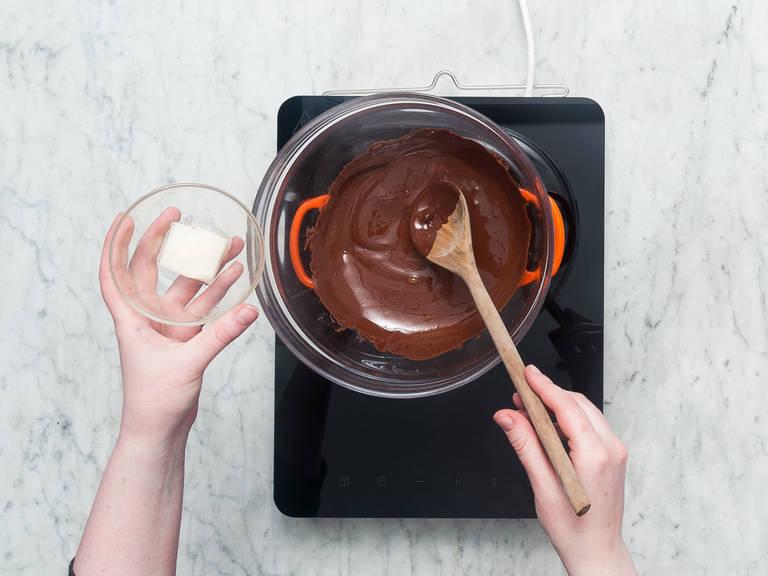 Schokolade hacken. Hitzebeständige Schüssel auf einen Topf mit kochendem Wasser stellen. Gehackte Schokolade in Schüssel schmelzen lassen und Kokosöl einrühren. Vom Herd nehmen und abkühlen lassen bis die Mischung lauwarm ist.