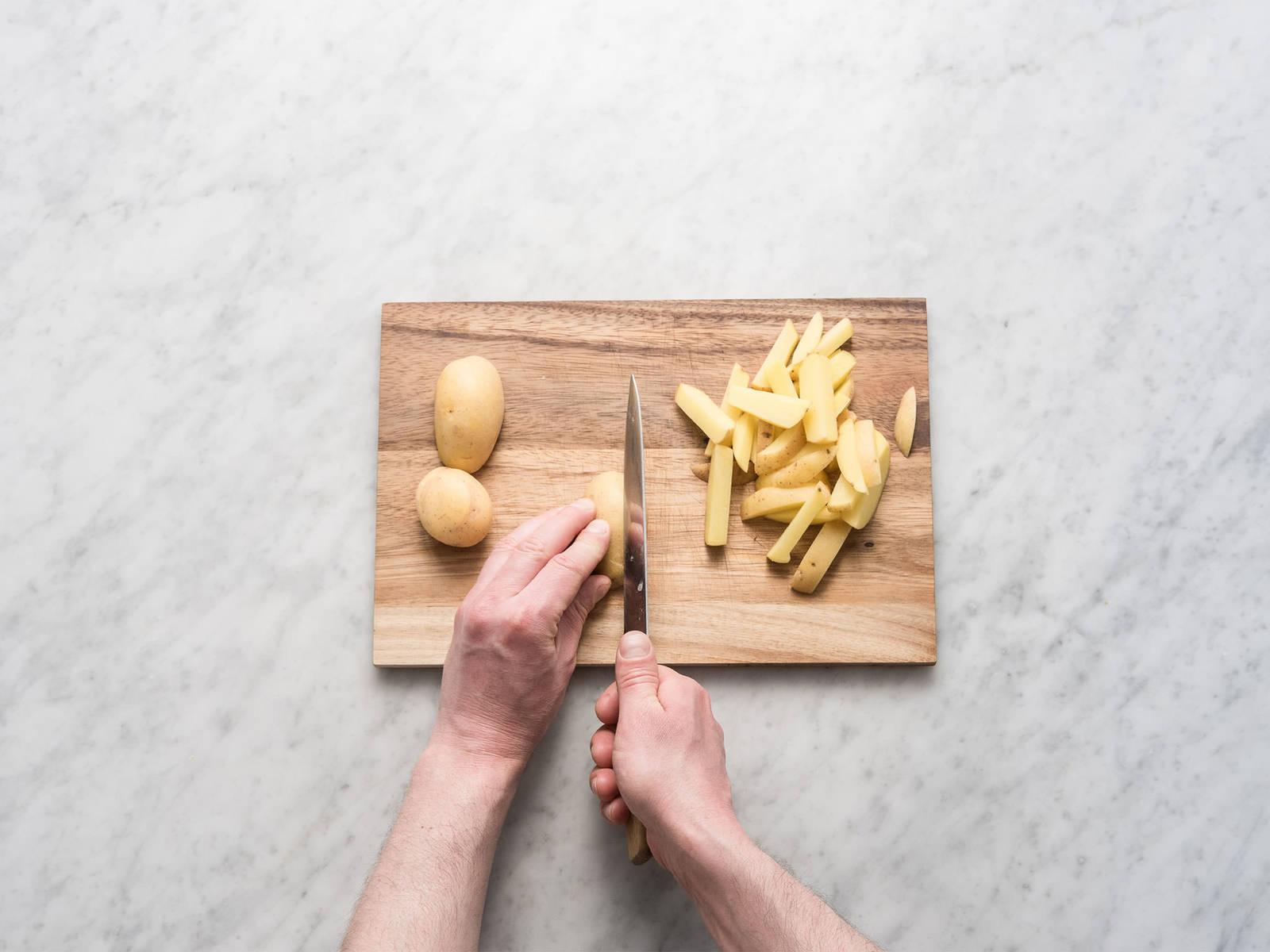 预热烤箱至200度。将土豆切成细条,放到大碗中与橄榄油、咖喱粉、圆肉豆蔻和熏盐一起搅拌。然后转移到铺好烘焙纸的烤盘中,在预热好的烤箱中以200度烤制25-30分钟,不时翻动,至土豆条外表焦脆金黄。