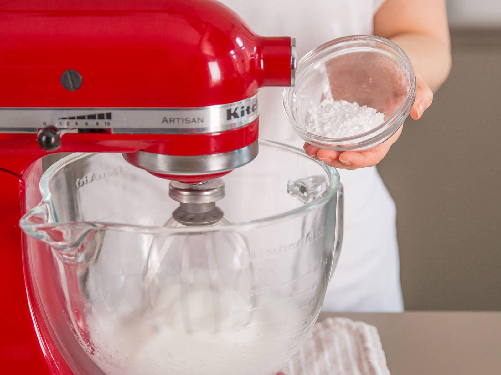 在蛋白中加一撮盐,搅打至硬性发泡。加入剩余糖粉,慢速搅拌。