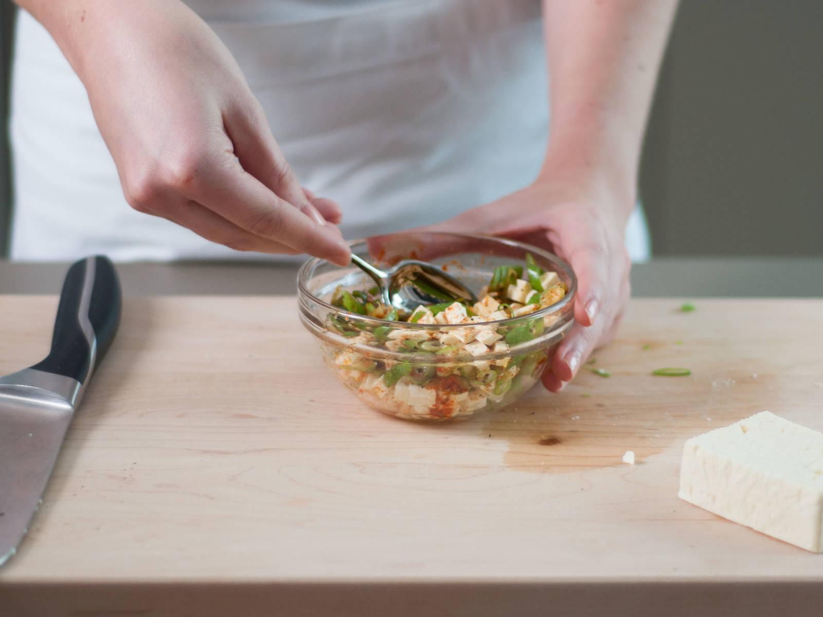 预热烤箱至180摄氏度。切碎洋葱,并将葱切细圈。向小碗中放入奶酪、甜椒粉、辣椒粉、植物油与小葱,混合均匀,并加入盐与胡椒粉调味。