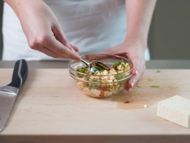 Backofen auf 180°C vorheizen. Schalotten fein würfeln und Frühlingszwiebeln in dünne Ringe schneiden. Schafskäse, Paprikapulver, Chiliflocken, Pflanzenöl und Frühlingszwiebeln in einer kleinen Schüssel vermengen. Nach Geschmack mit Salz und Pfeffer würzen.