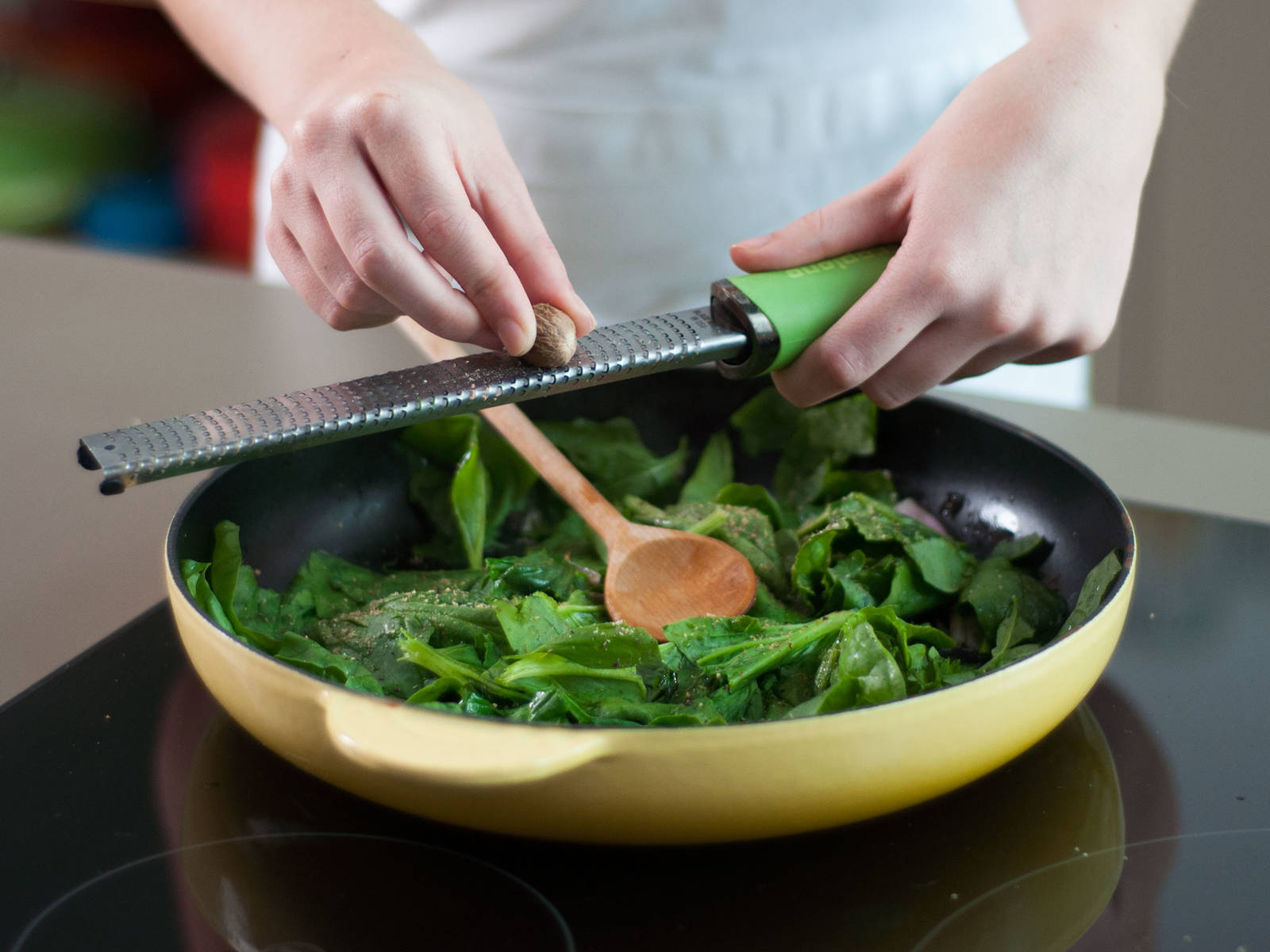 向大煎锅中注入适量植物油,用中温加热,放入洋葱碎煸炒1-2分钟。然后加入菠菜,继续煸炒1-2分钟至菠菜变软。向锅中擦入肉豆蔻并搅拌均匀,停止加热。