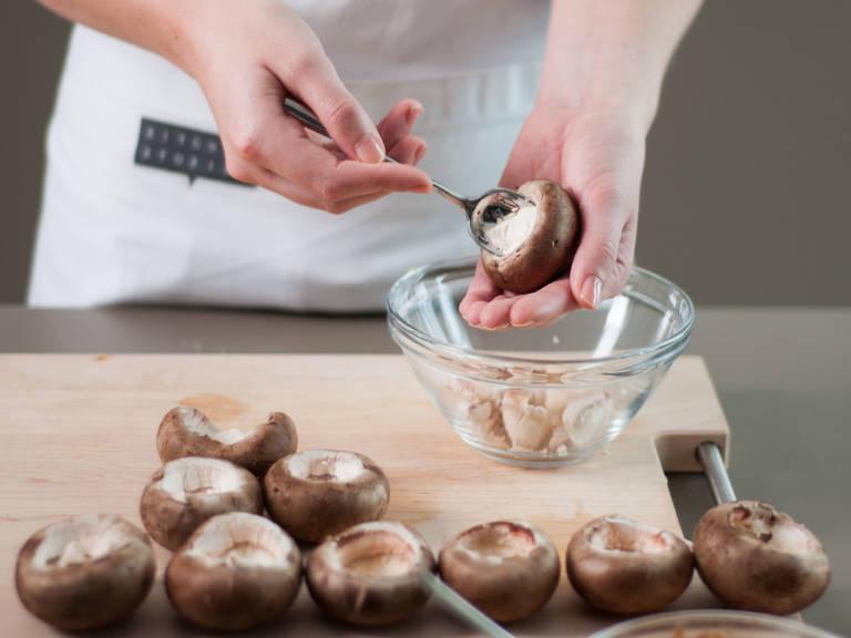 Vorsichtig die Pilzstiele von den Pilzhüten trennen. Anschließend das Innere des Huts mit einem Löffel entfernen, um Platz für die Käse- und Spinatmischung zu schaffen.