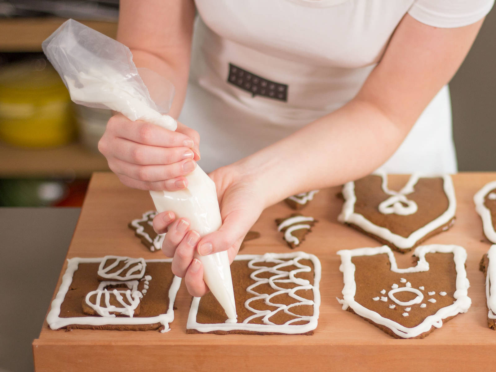 Meanwhile, mix confectioner's sugar with just enough water to form a thick icing. Once pieces have cooled, decorate with icing using a piping bag. If desired, decorate with sprinkles or other edible decorations. Set aside to dry completely.