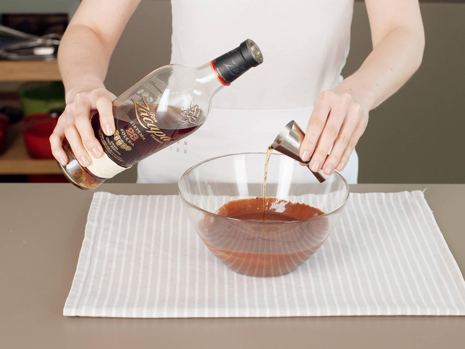 Backofen auf 150°C vorheizen. Sahne in einem kleinen Topf bei mittlerer Hitze zum Kochen bringen. Schokolade in eine große Schüssel geben und Sahne hinzugeben. Rühren, bis die Schokolade geschmolzen ist und sich mit der Sahne verbunden hat. Vor dem nächsten Schritt, mit einem Küchenthermometer sicherstellen, dass die Masse auf 35°C heruntergekühlt ist. Butter und Rum hinzufügen und rühren, bis die Ganache eine gleichmäßige Konsistenz aufweist.