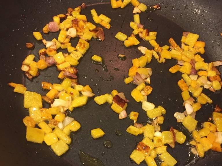 将灯笼椒、洋葱和番茄切丁。在一个煎锅中,加热些许橄榄油。然后倒入灯笼椒和洋葱,翻炒至稍微变棕色。