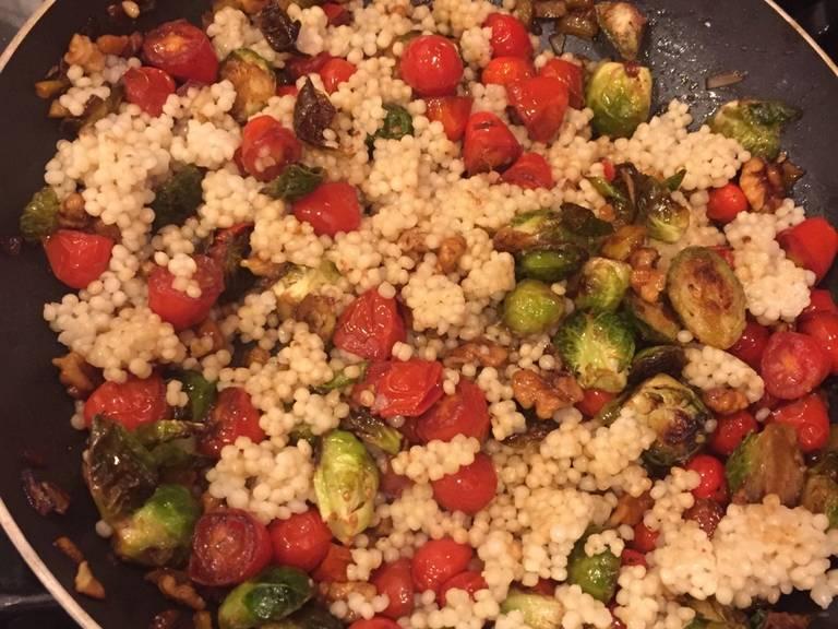 倒入粗麦粉,搅拌均匀。倒入剩余的橄榄油,撒盐与胡椒调味。