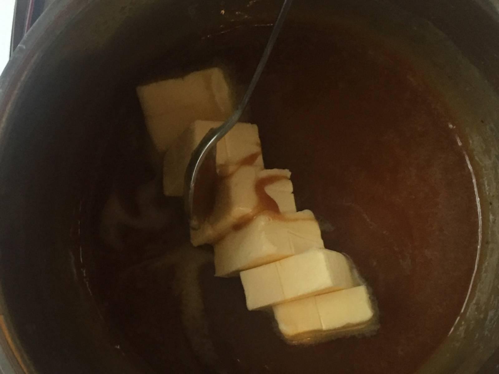 Sobald eine homogene Masse entstanden ist, mit dem Zuckerthermometer prüfen und bei 108°C den Topf vom Herd nehmen. Nun die zerkleinerte, gesalzene Butter hinzugeben und zu einer glatten Creme rühren.